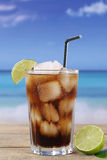 Cola in glass with lime on the beach Stock Photography