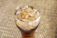 Cola in glass on woven bamboo background Stock Images