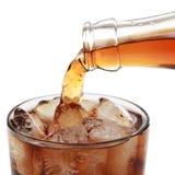 Cola som häller in i ett exponeringsglas som isoleras Royaltyfria Bilder