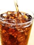 Cola i den glass koppen med läskfärgstänk Arkivfoto