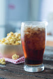 Cola i exponeringsglas med popcorn royaltyfria bilder