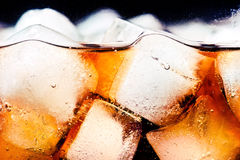 Cola with ice. Glass of cola with ice cubes close-up royalty free stock photography