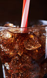 Cola with ice cubes close up. Cola with ice cubes and plastic tube. close up Royalty Free Stock Image