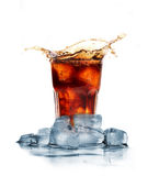 Cola with ice cubes splashing Royalty Free Stock Photography