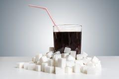 Cola im Glas und viele zuckern Würfel herum Ungesundes Essenkonzept Lizenzfreie Stockfotos