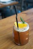 Cola med den orange coctailen på trätabellen Arkivfoto