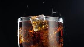 Cola med isbakgrund Stort exponeringsglas av kall cola med närbild för iskuber stock video
