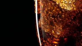 Cola med isbakgrund Stort exponeringsglas av kall cola med närbild för iskuber 4K arkivfilmer