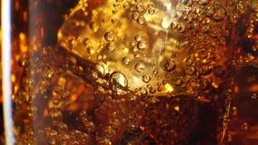 Cola med isbakgrund Stort exponeringsglas av kall cola med närbild för iskuber 4K lager videofilmer