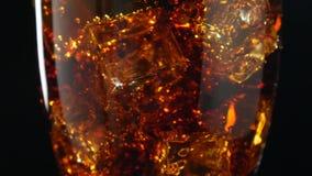 Cola med isrotation Stort exponeringsglas av kall cola med närbild för iskuber arkivfilmer