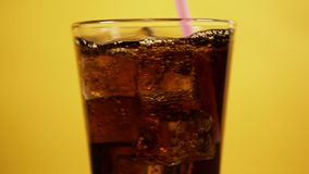 Cola mescolantesi con cannuccia rosa Vetro pieno dei cubetti di ghiaccio gassate della bevanda del coke video d archivio