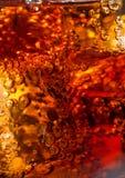 Cola no vidro com gelo e bolhas do gás Fotos de Stock Royalty Free