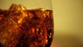 Cola no vidro com os cubos e as bolhas de gelo que giram Fundo do alimento Close-up da soda filme