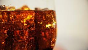 Cola no vidro com os cubos e as bolhas de gelo que giram Fundo do alimento Close-up da soda video estoque