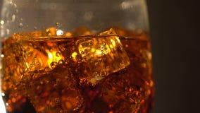 Cola no vidro com os cubos e as bolhas de gelo que giram Fundo do alimento Close-up da soda vídeos de arquivo