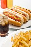 Cola, patate fritte e tre hot dog Immagini Stock Libere da Diritti