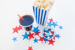 Cola and popcorn with candies on independence day. American independence day, celebration, patriotism and holidays concept - close up of coca cola cup, popcorn Stock Photos