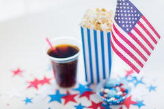 Cola and popcorn with candies on independence day. Celebration, patriotism and holidays concept - close up of american flag, coca cola cup, popcorn and candies Stock Image