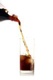 Cola pour into glass on white Stock Photography