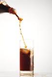 Cola pour into glass on white Stock Photos