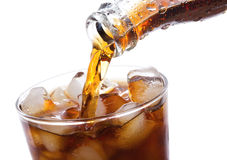 Cola is pouring into glass. On white background Stock Photography