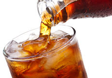 Cola is pouring into glass. On white background Royalty Free Stock Photos