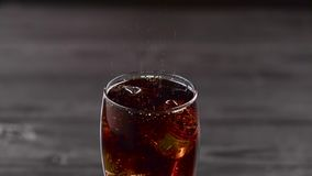 Cola pouring into glass with ice cubes. Close up. Cola pouring into glass with ice cubes standing on a dark table. Close up stock video