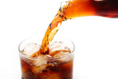 Cola pouring into glass. On white background Royalty Free Stock Images