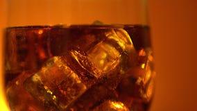 Cola que derrama no vidro com cubos e bolhas de gelo Fundo do alimento Close-up da soda filme