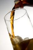 Cola que vierte en el vidrio con hielo Imagen de archivo libre de regalías