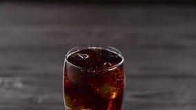Cola que vierte en el vidrio con los cubos de hielo Cierre para arriba almacen de video