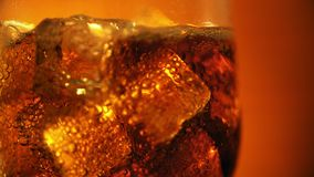 Cola que vierte en el vidrio con los cubos y las burbujas de hielo Fondo del alimento Primer de la soda almacen de video