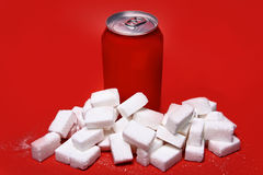 Cola refreshing drink can and lot of white sugar cubes represent Stock Photo