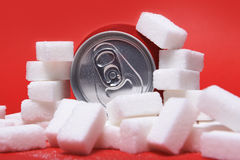 Cola refreshing drink can and lot of white sugar cubes representing the big amount of calories Royalty Free Stock Images