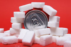Cola refreshing drink can and lot of white sugar cubes representing the big amount of calories Stock Photo