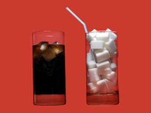 Cola refreshing drink and glass full of sugar cubes and straw representing massive calories content Stock Photo