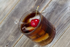 Cola and Rum with ripe cherry and ice in Glass Royalty Free Stock Image