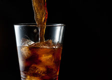 Cola som häller in i iced exponeringsglas Arkivfoton