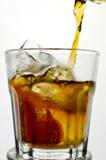 Cola som in hälls till ett exponeringsglas från en höjd Arkivbild