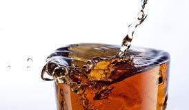 Cola splash. Dramatic cola splash isolated on white royalty free stock image