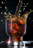 Cola splash. Splashed cola with ice on black background stock images