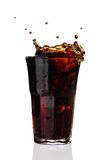 Cola splashing out of glass. Isolated on whte background stock images