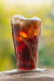 Cola water pouring into glass with ice cubes on sand Stock Photo
