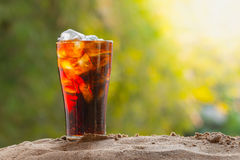 Cola water pouring into glass with ice cubes on sand Stock Photography