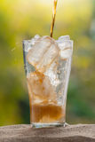 Cola water pouring into glass with ice cubes on sand Royalty Free Stock Image