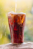 Cola water pouring into glass with ice cubes on sand Stock Image