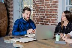 Colaboración de los sitios de los desarrolladores del hombre y de la mujer junto en oficina, usando el red-libro imagen de archivo