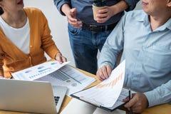 Colaboración del equipo del negocio que discute trabajando analizar con datos financieros y comercializando el gráfico del inform imagenes de archivo