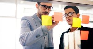 Colaboración y análisis por los hombres de negocios que trabajan en oficina foto de archivo