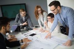 Colaboración y análisis por los hombres de negocios que trabajan en oficina imagenes de archivo